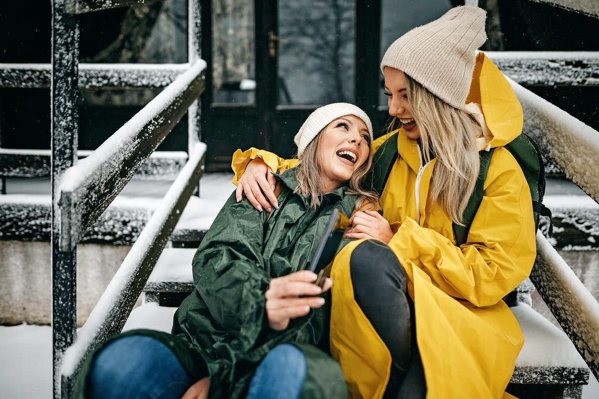 A happy couple laughs while sitting on the snowy steps of a winter cabin.