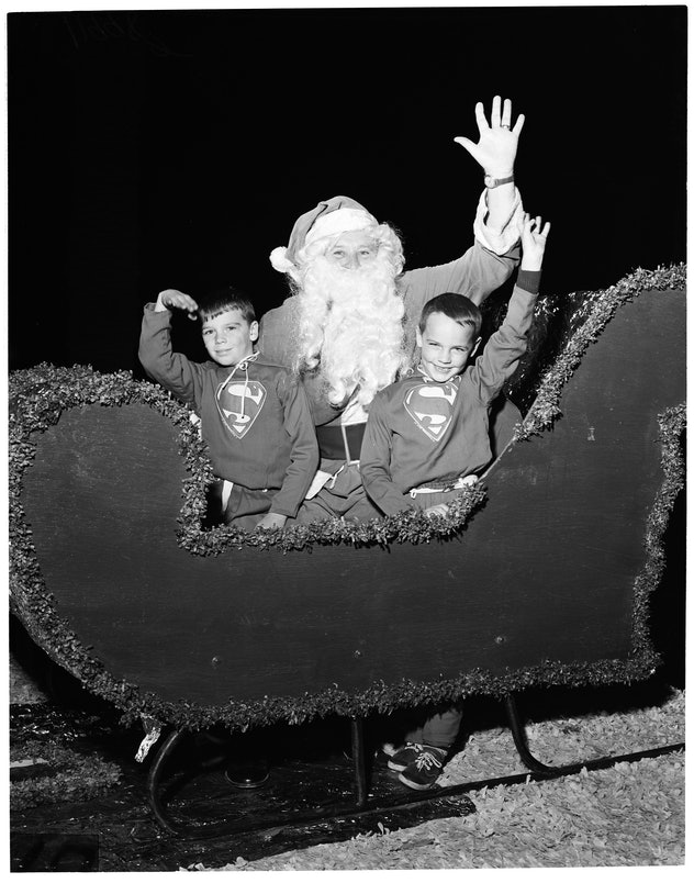 This vintage Christmas photo shows two boys riding in Santa's sleigh during a parade.