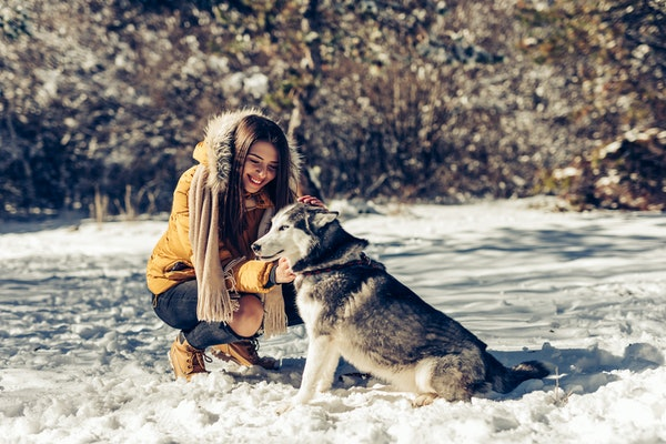 A happy woman kneels next to her husky in the snow.