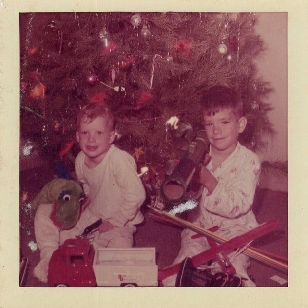 This vintage Christmas photo shows two brothers opening gifts.