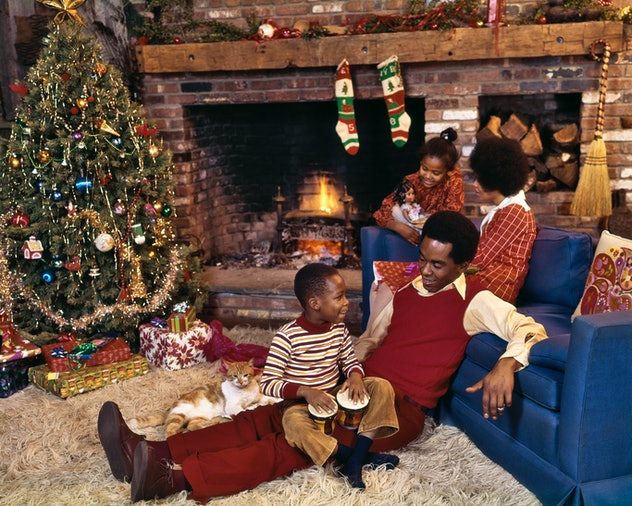 This vintage Christmas photo features a family relaxing in front of the fireplace.