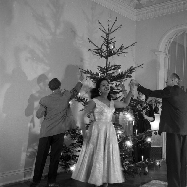 This vintage Christmas photo from 1955 shows people dancing in front of a tree.