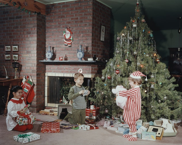 Playing in front of the tree is a classic scene in this vintage Christmas photo.