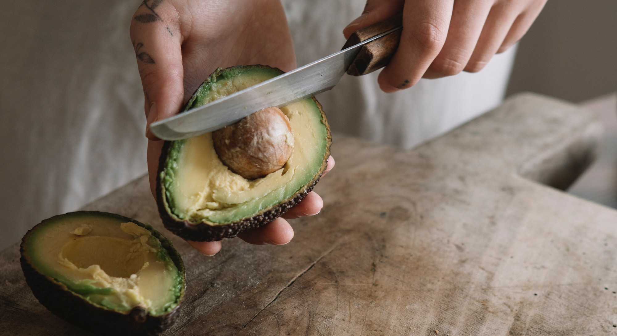 A woman cuts an avocado after a new study found that avocado can help your gut health.