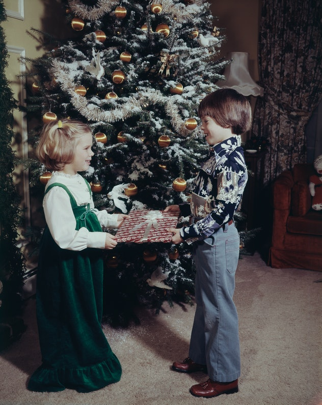 This vintage Christmas photo shows two children exchanging gifts.