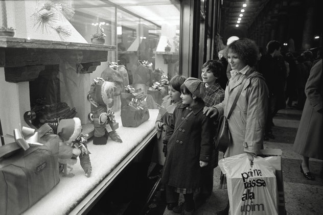 This vintage Christmas photo shows a mom and kids window shopping.