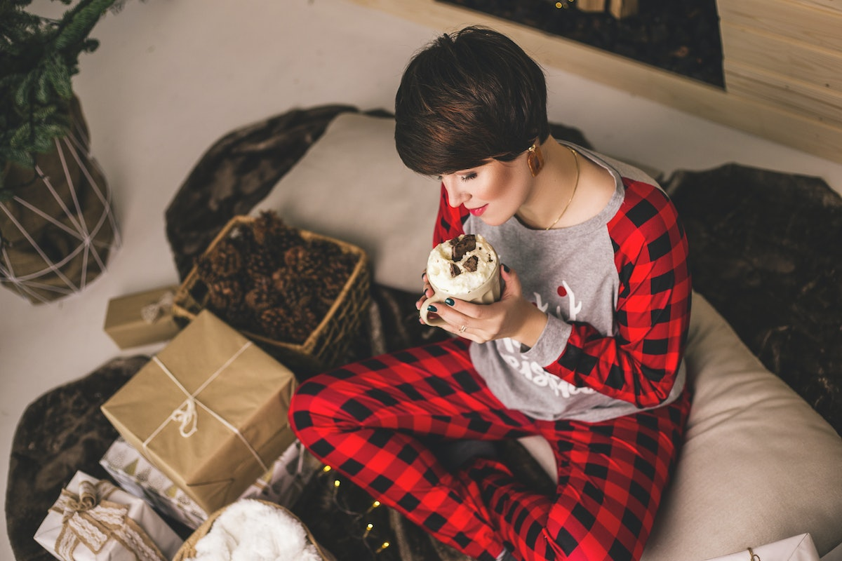 A happy woman in Christmas pjs sips a hot chocolate next to presents.