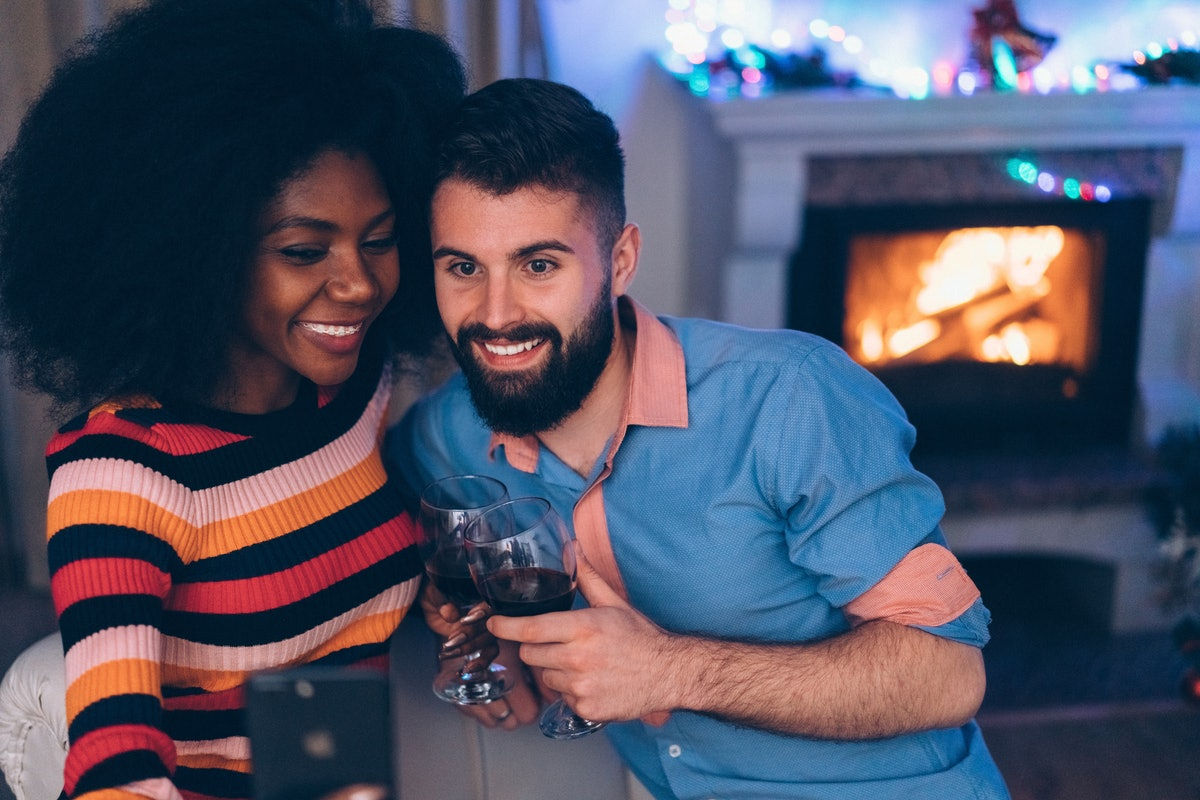 A couple takes a selfie with wine glasses next to their fireplace in the winter.