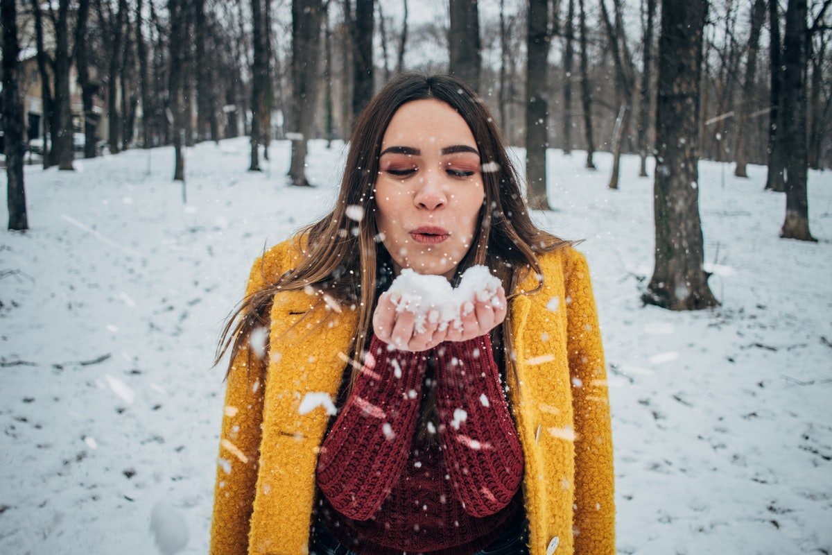 A woman in a yellow coat and red sweater blows on a snowball in the winter.