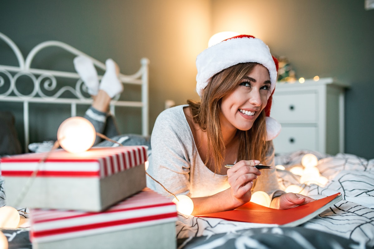 A happy woman writes out a Christmas card on her bed.