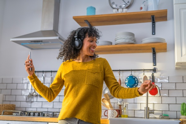 A happy woman dances with her headphones on, as she films herself on her phone.