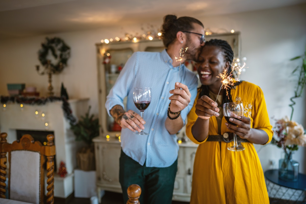 A happy couple celebrates the new year with sparklers and wine glasses.