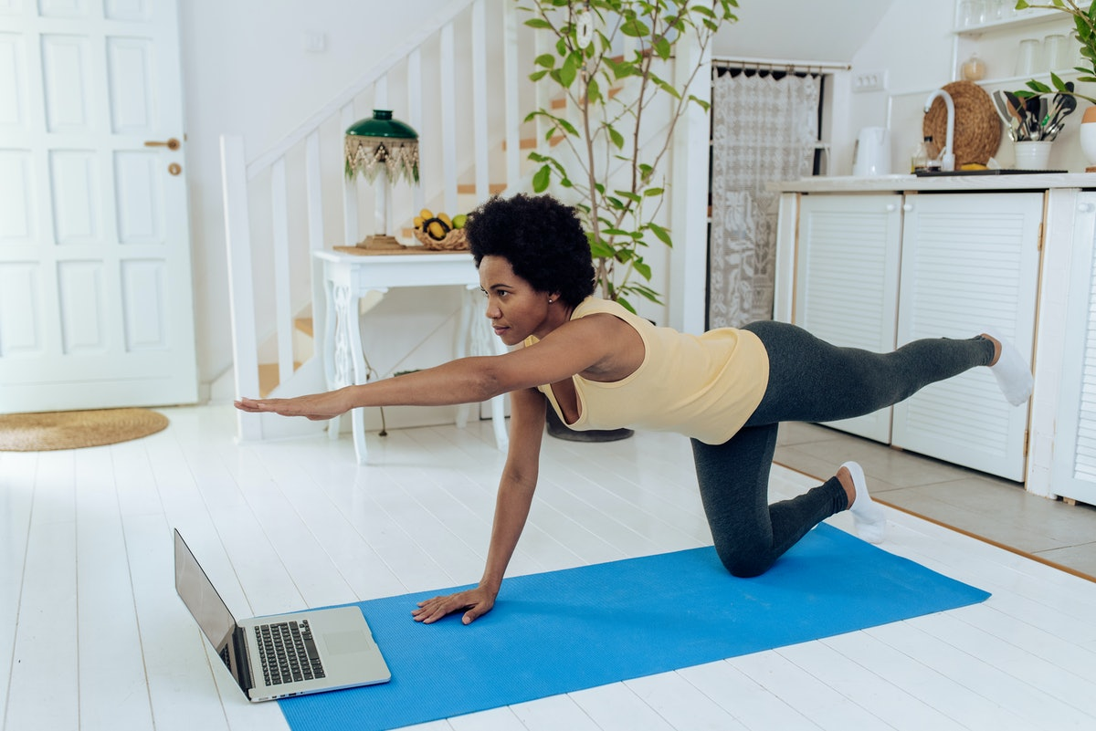 A woman does virtual yoga in her home.