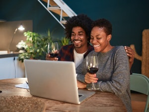 A happy couple holds red wine glasses while looking at their laptop at home.