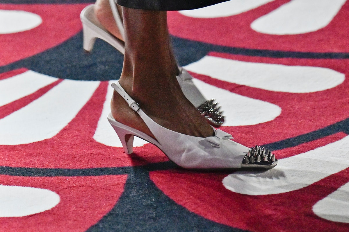 a model on the runway wearing white slingback studded kitten heels, a retro shoe trend for 2021