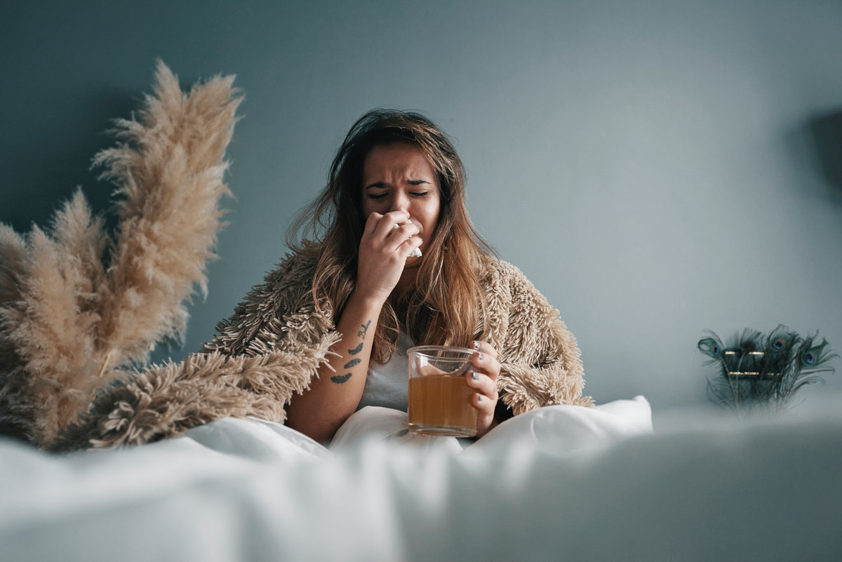 A woman sits in bed looking ill.