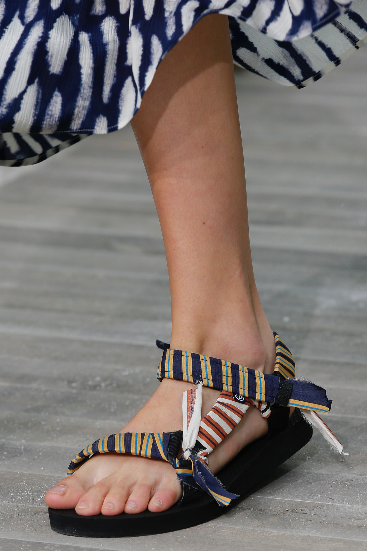 A model's foot in a striped, fabric-covered sport sandal, a 2021 shoe trend making a comeback