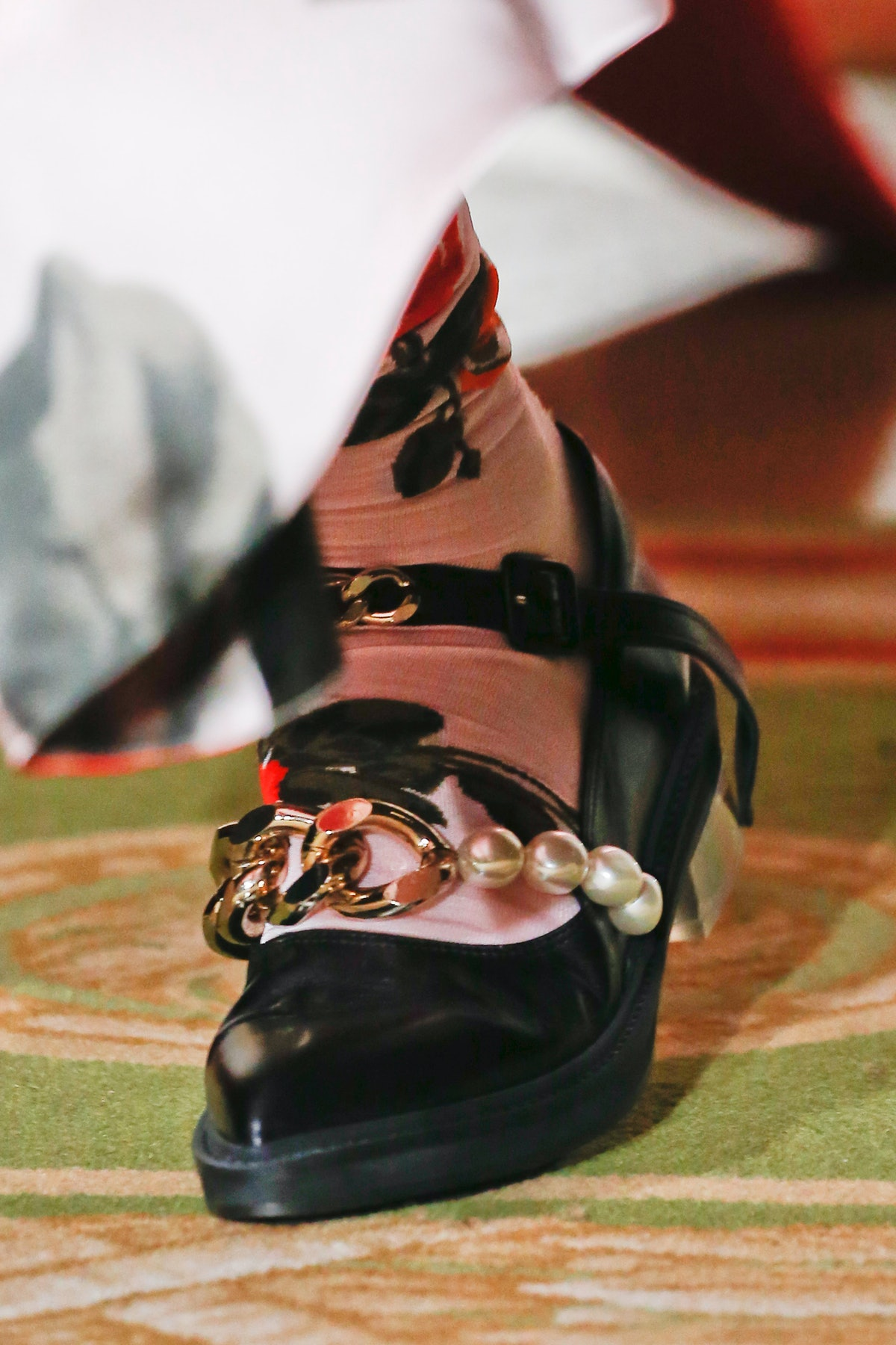 A model wearing a black ballet flat shoe on the runway, demonstrating a 2021 shoe trend