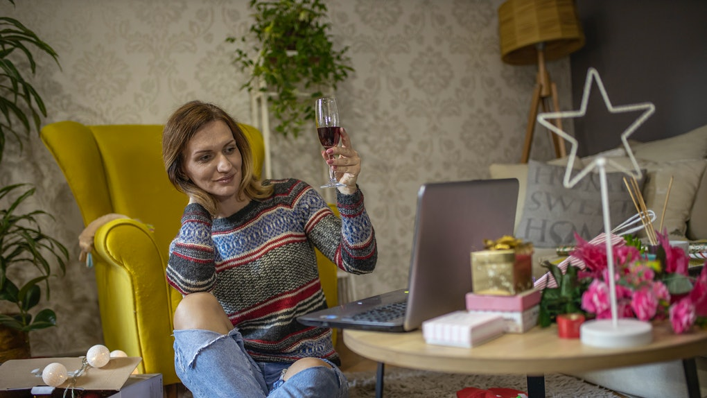 A woman in a sweater and jeans raises her champagne flute while having a virtual New Year's Eve celebration.