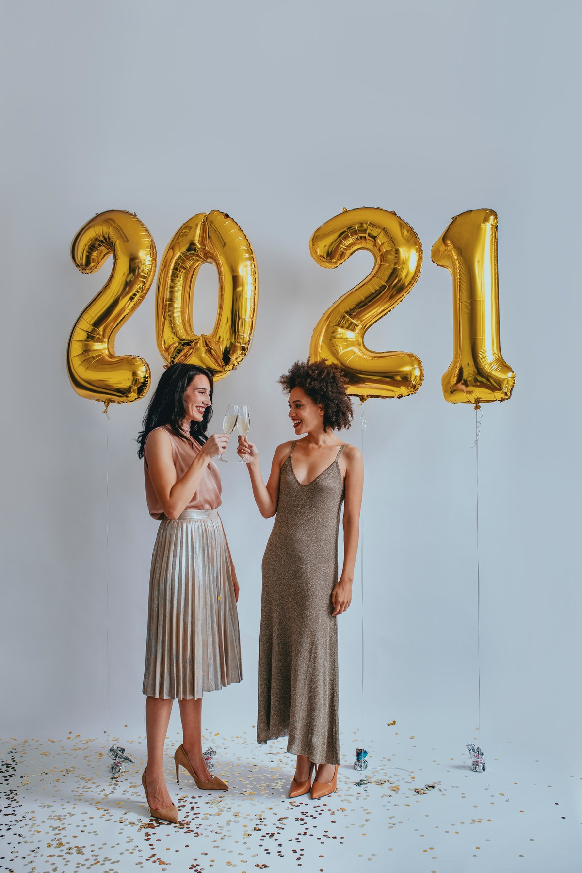 Two friends clink their glasses while standing next to gold, 2021 balloons on New Year's Eve.