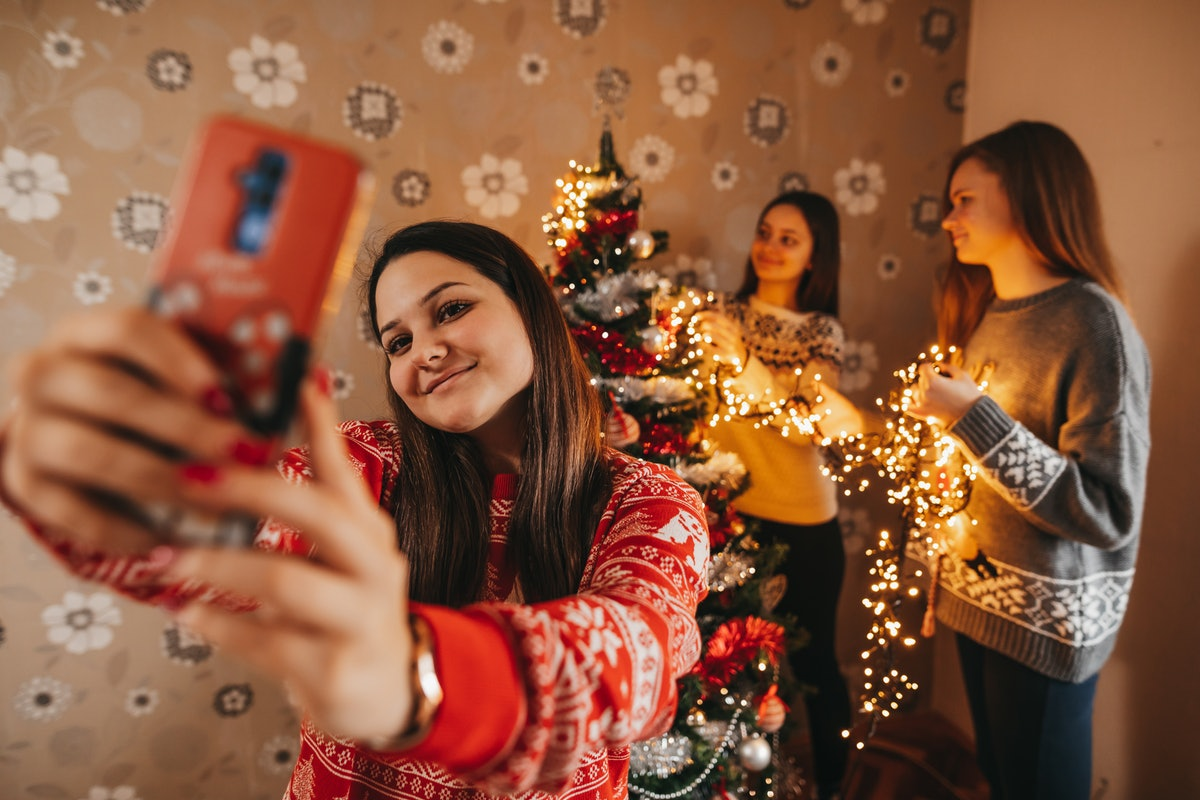 Three sisters show off their Christmas decorations while wearing holiday sweaters and participating in a virtual party.