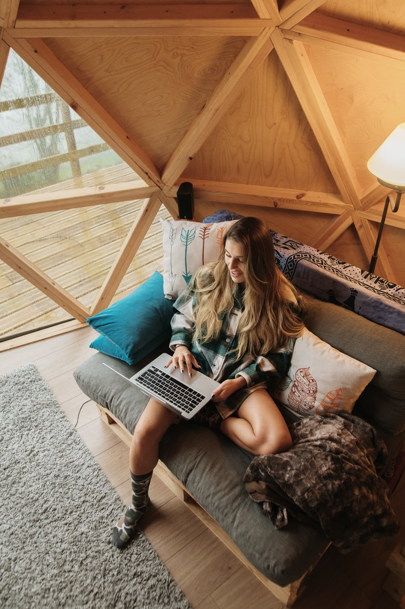 A woman in a yurt works on a laptop. These holiday 2020 staycation ideas will scratch your travel itch, experts say.