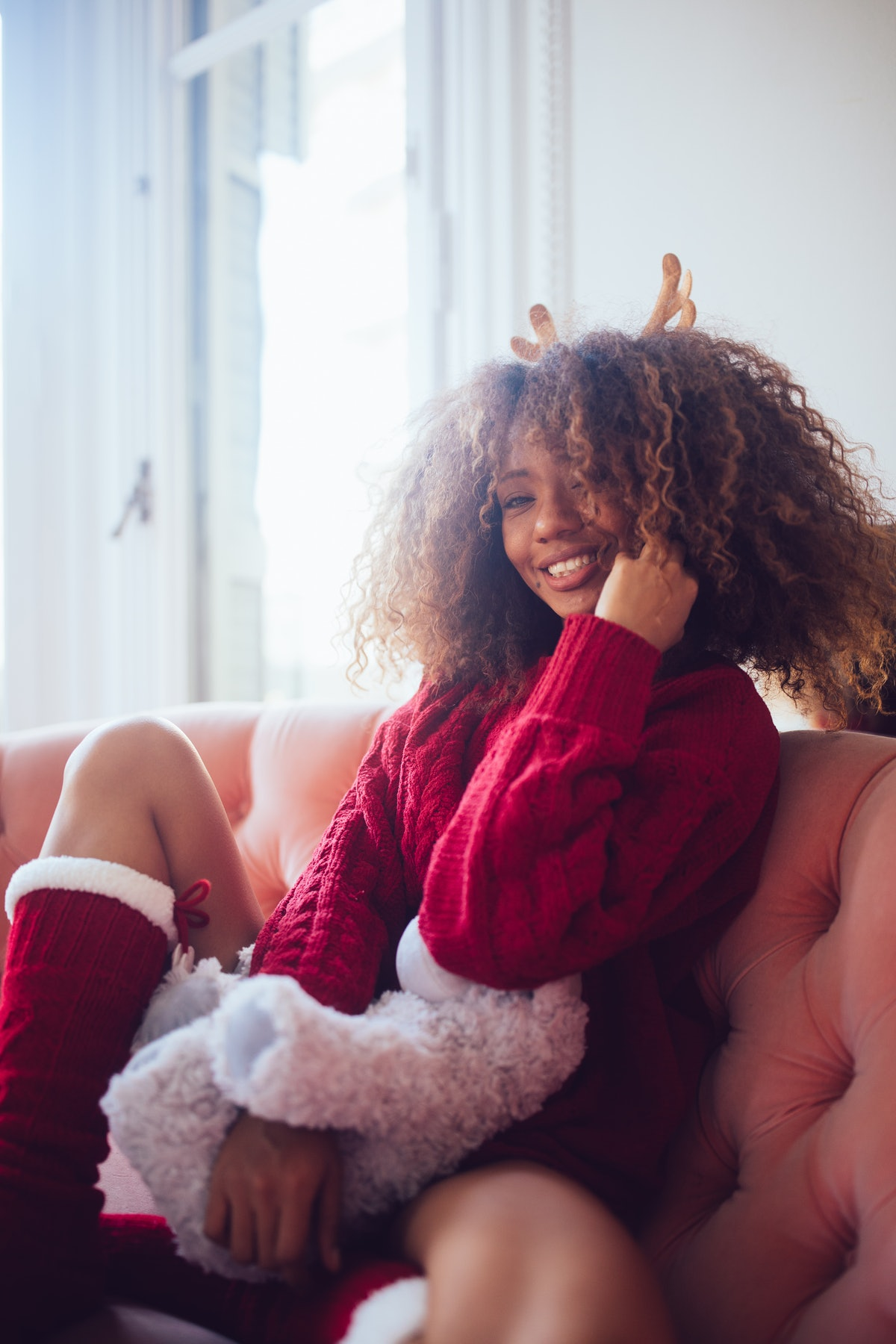 A young Black woman poses in a Christmas sweater and socks while attending a virtual Christmas party.