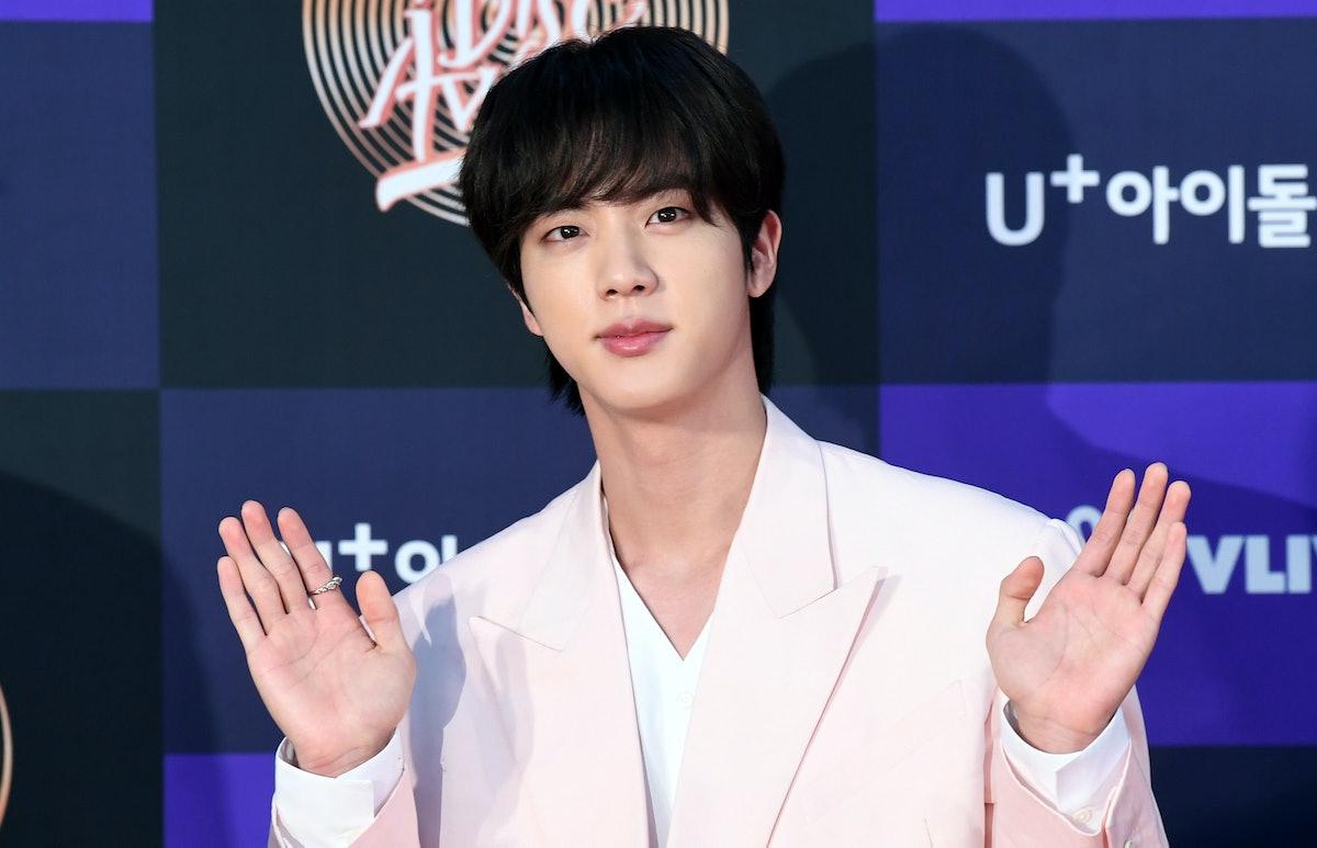 BTS' Jin waves to fans.