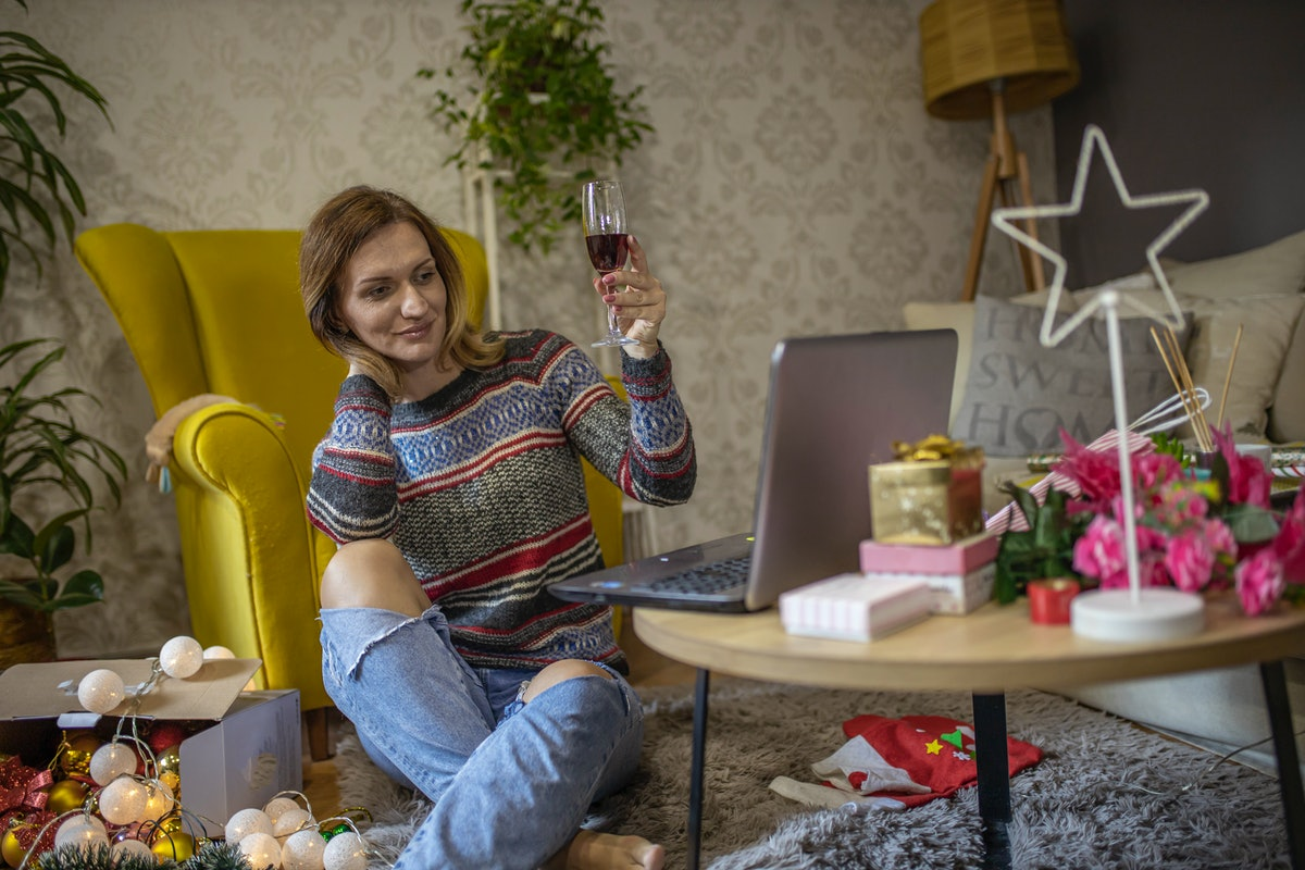 A woman holds up her glass of red wine while looking at her laptop in her festively-decorated living room.