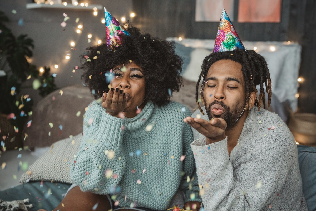 A couple in their loungewear blow confetti in their home for New Year's Day.
