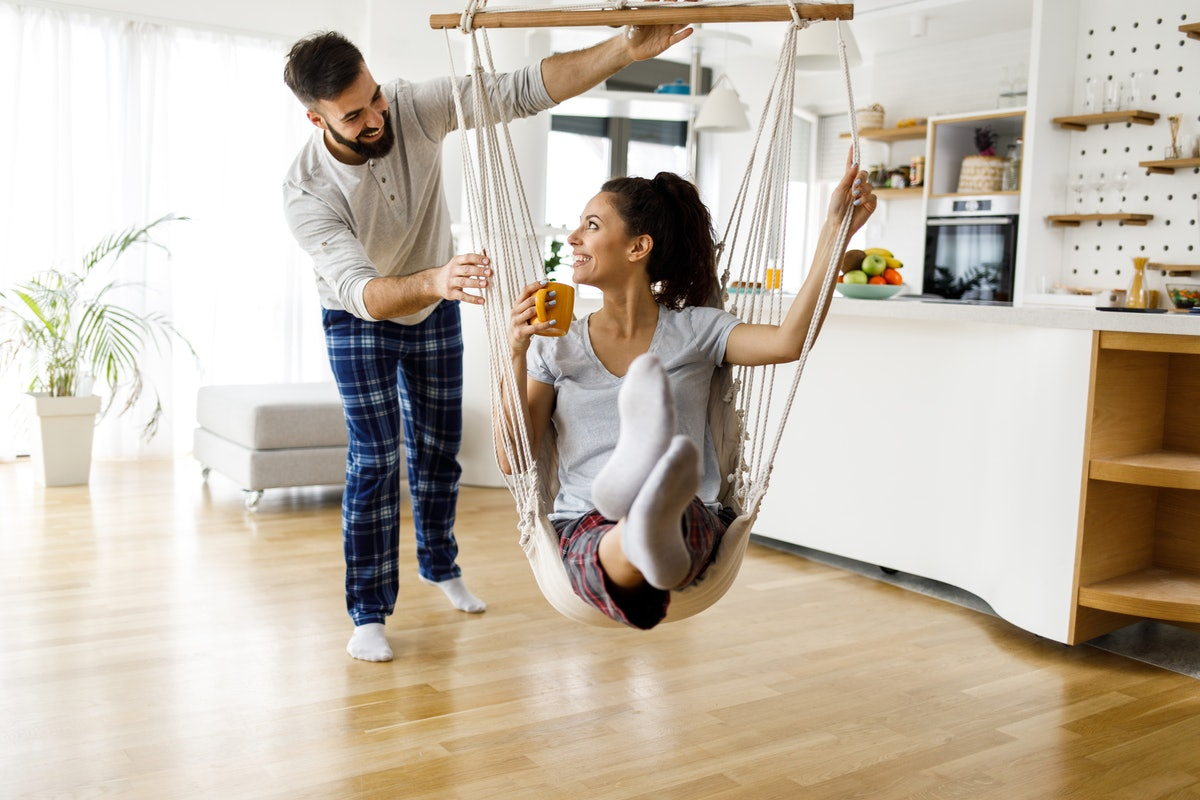 A young couple plays with a swing in their living room while wearing loungewear on New Year's Eve.