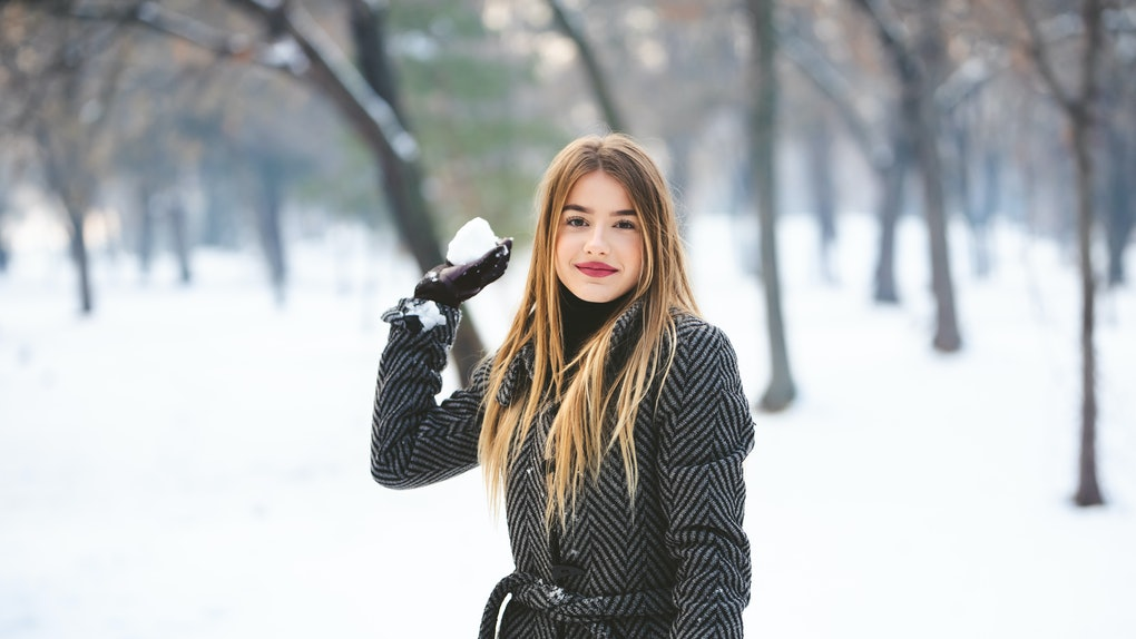 A trendy woman with a peacoat on holds a snowball.