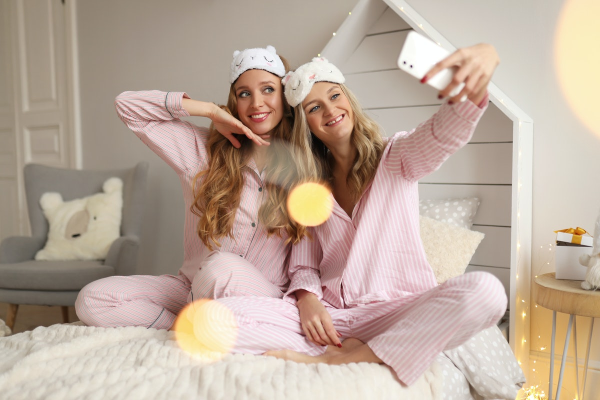 Two friends in matching pink pjs take a selfie on a bed.
