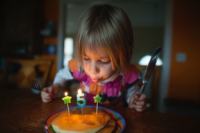 girl blowing out birthday candles number 5