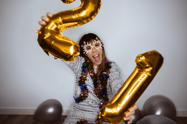 A happy woman holds up a two and one balloon while celebrating the new year at home.