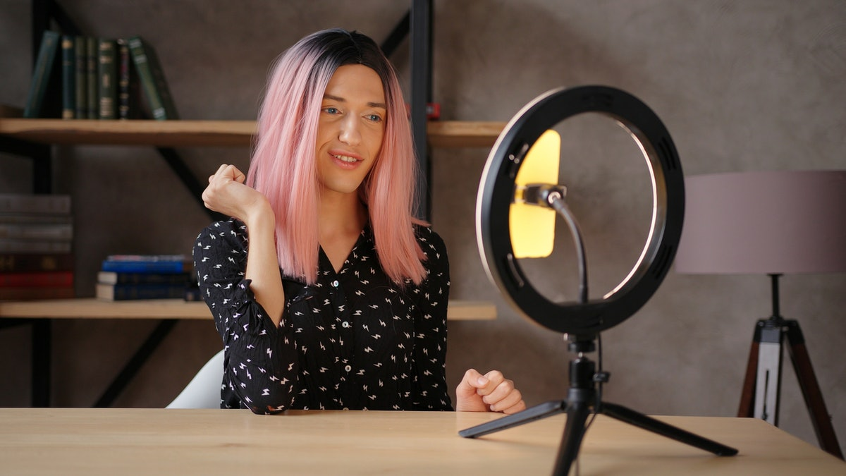 A happy woman with a black and white blouse and pink hair takes a selfie using a ring light and phone stand.