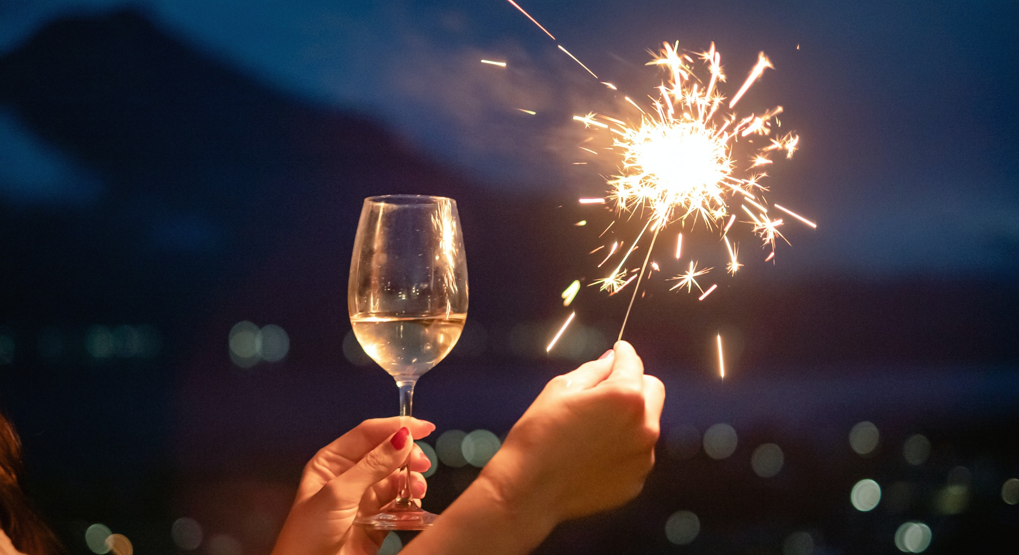 close up of a hand with champagne and a sparkler