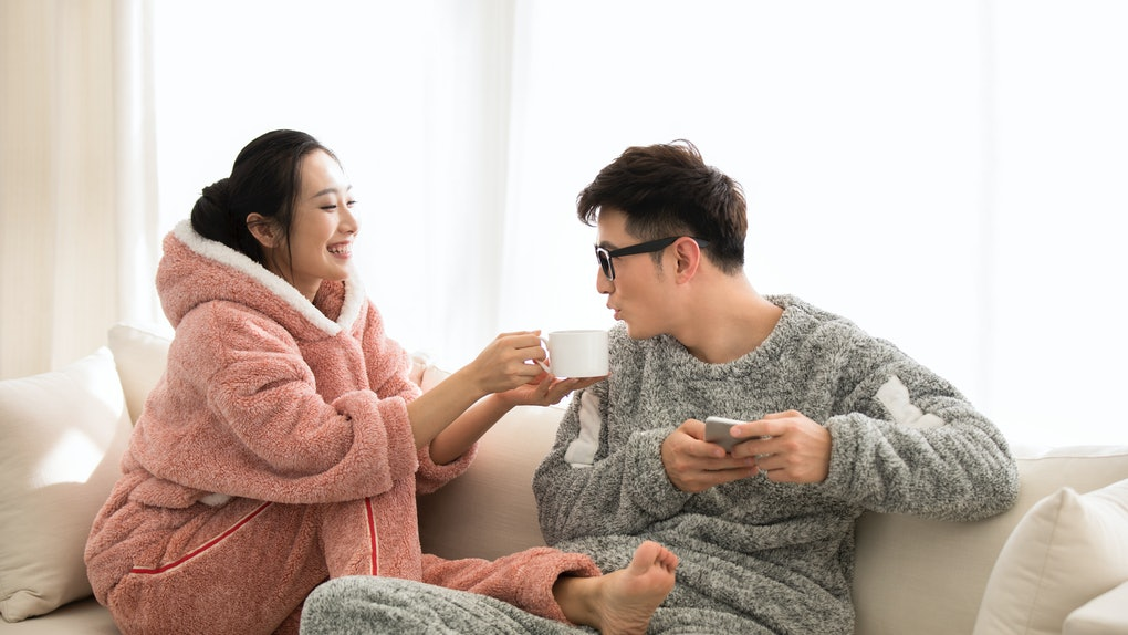 A couple in fuzzy onesies lounge on the couch, sipping warm drinks.