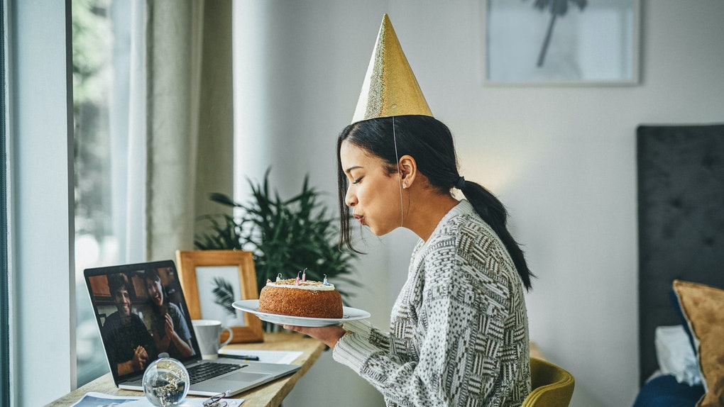 A young woman blows out candles on a cake, while attending a virtual birthday party for adults and wearing a party hat.