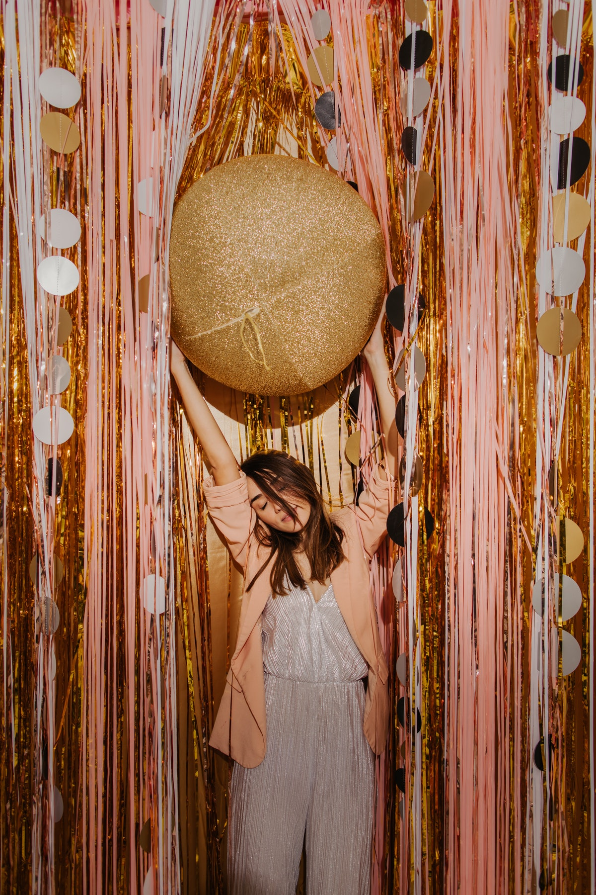 A young woman wears a sparkly jumpsuit, and stands next to pink and gold streamers while holding a glittery ball above her head.