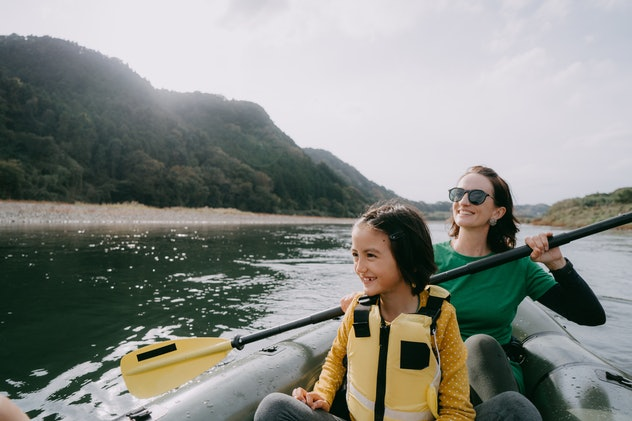 A woman and a young girl kayak on a river among rolling green hills.