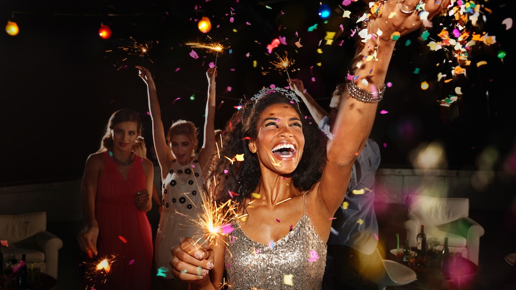 A young Black woman throws confetti in the air while holding a sparkler on a throwback New Year's Eve.