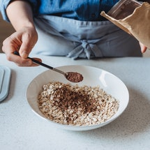 A person wearing a blue apron sprinkles cinnamon on oatmeal. The health benefits of cinnamon are manifold, a nutritionist tells Bustle