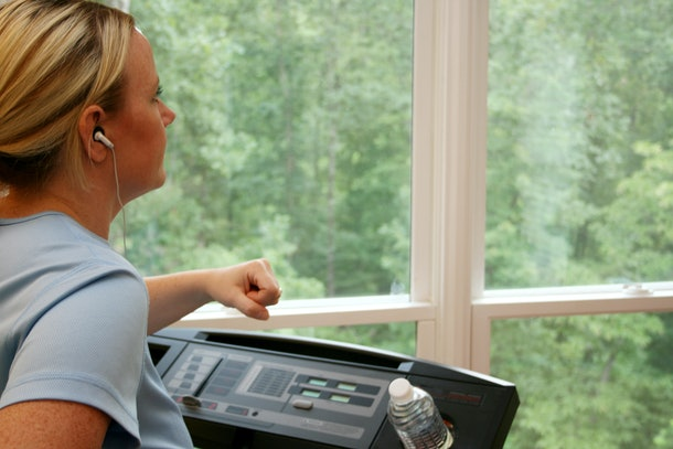 A blonde woman walks on her treadmill at home.