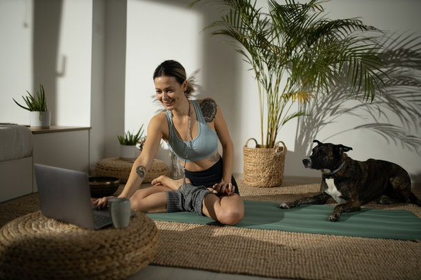 A young woman gets ready to take a virtual Zumba class on her laptop while sitting on her living room floor with her dog.