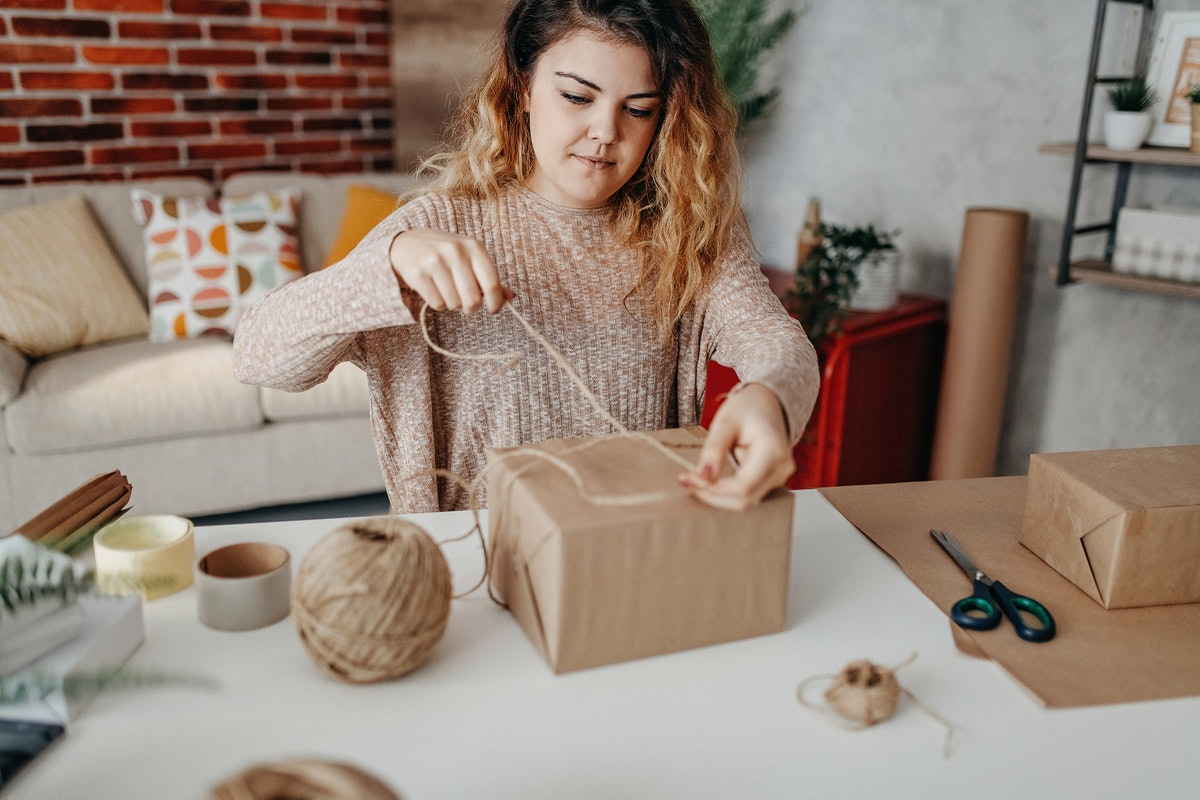 A young woman ties twine onto a Hanukkah gift wrapped in brown paper.