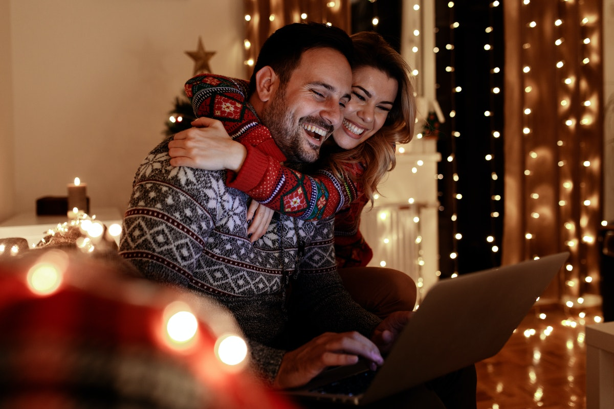 A happy and festive couple embraces while shopping online for the holidays.