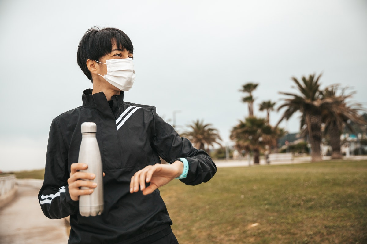 A person holds a water bottle and checks their watch while out for a run wearing a mask. Exercise isn't all about long workout sessions, the WHO says.