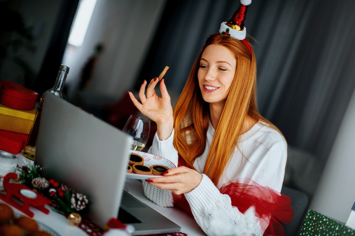 A happy woman wearing a Santa hat holds a plate of Christmas cookies while chatting with friends on Zoom.