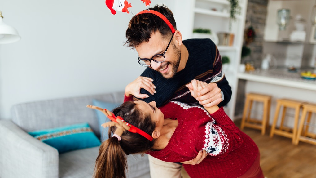 A happy festive couple dances to Christmas music in their home.
